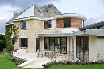 Image showing the exterior of the house from the garden.  The image shows how the terne-coated stainless steel roofing and curved timber boarding juxtapose the local Bath stone ashlar, render and clay roof tiles.