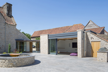 Photograph highlighting the view from the new landscaped terrace leading into the new garden room with has large pocket doors doors to create a much improved relationship between the house and the garden.