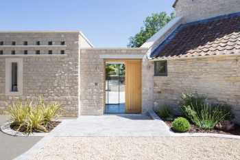 Photograph of the approach to the new extended part of the house, timber doors greet vistitors behind which large glass doors open out on to landscaped garden.