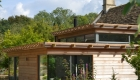 Photograph showing the completed cedar clad 1.5 storey extension against the existing listed building.