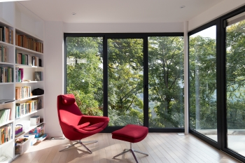 Photograph of the interior view of the writing room, a large red chair is positioned with views out towards the greenery beyond. The room has large full height glazing and sliding doors opening onto raised terrace deck.