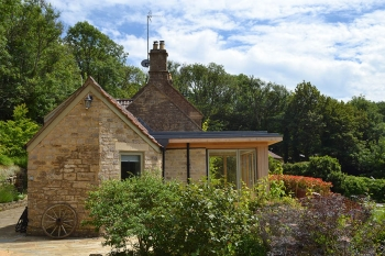 Image showing gable of existing stone cottage with contemporary stone and glass flat roofed extension overlooking garden