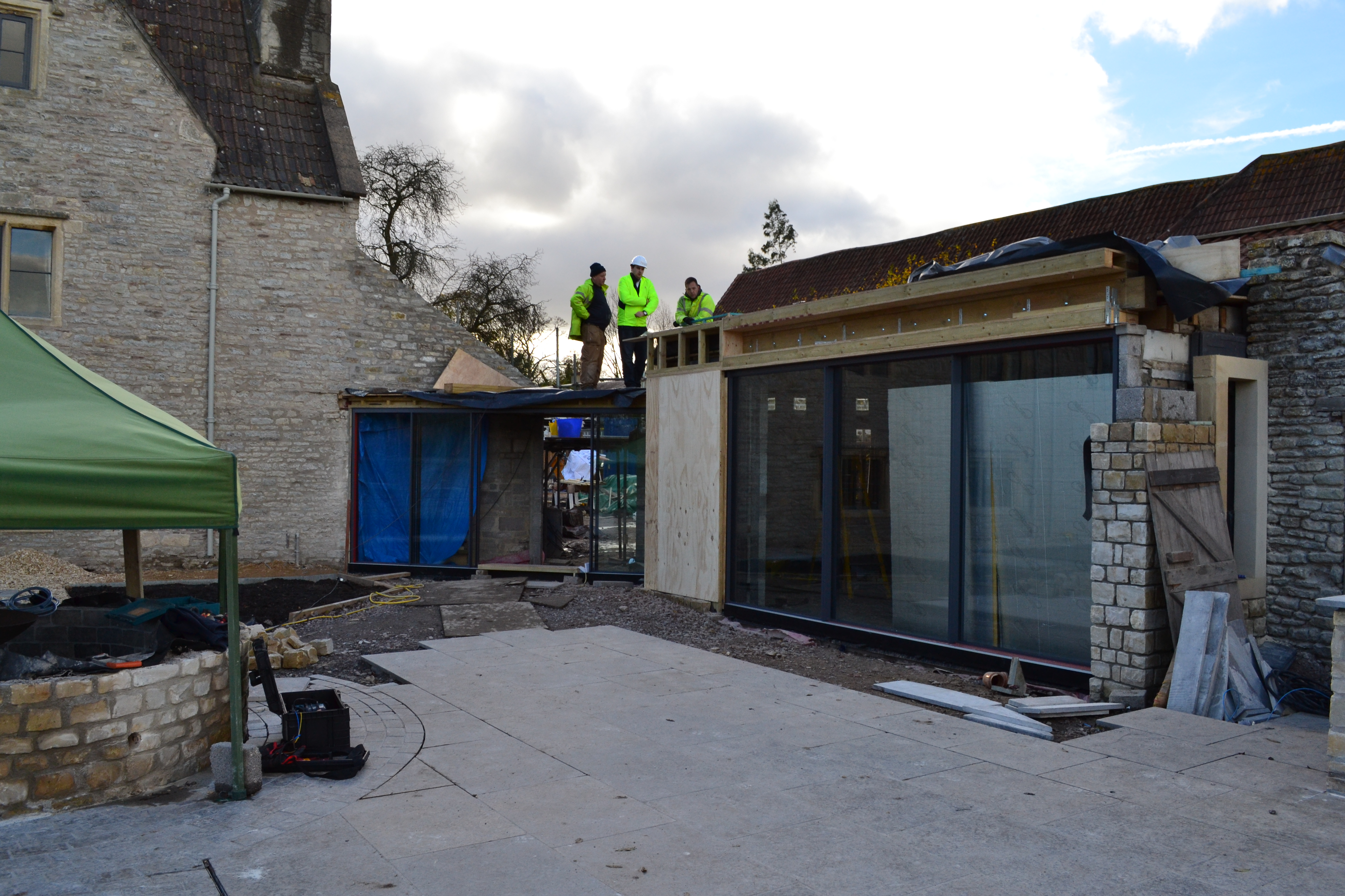Image showing hetreed ross architects on site in branded hi-vis and hard hats against the backdrop of Listed Manor House Grade ll* Listed Extension