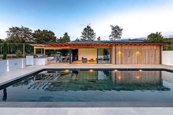 Image showing the exterior of the contemporary swimming pool and poolside building with natural timber cladding