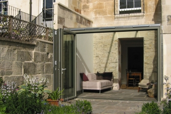 External image of the exterior of a contemporary conservatory extension to a Georgian house in Bath, showing the glass bi-fold doors and seamless transition from the house to the courtyard garden.