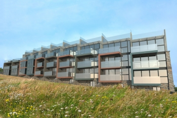 Image showing the cliff side exterior of the contemporary development designed by Hetreed Ross. The images shows how the low maintenance materials such as zinc, natural stone and acetylated timber create a harmony between the scheme and the surrounding environment.
