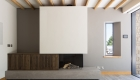 Internal photograph of the contemporary fireplace comprising of concrete base with timber storage and a large contrasting protruding white box as the chimney breast.