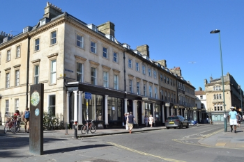 Photograph taken from the corner of Queen Square, Bath looking back up at wood street showing the external elevation of the Georgian building, with apartments on the top three floors and commercial office space below.