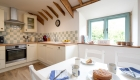 Photograph visualising the open plan kitchen/dining space of one of the country cottage aesthetic kitchens.