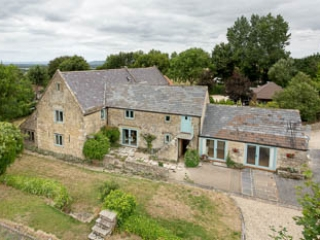 External photograph taken from the neighbouring iron age fort, lookig down on the large series of Cotswold barns.