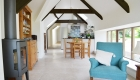 Internal photograph of the open plan linear living space with exposed beams.