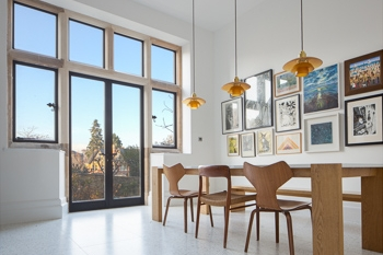 Interior photograph highlighting the light and paired back architectural approach to the dining room with the focus on the large glazing and gallery wall.