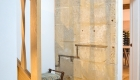 Image showing foot of internal stairs with mustard coloured carpet and area of Bath stone exposed on internal wall
