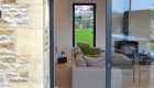 View looking through sliding aluminium patio doors into living room with Bath rubble stone walls and timber soffit