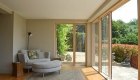 Image showing mdoern grey sofa in new garden room lit by light coming in through full height windows