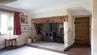 Image of a traditional fireplace stack with oak beams, carved plaster and traditional door
