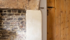 Zoomed image of a traditional fireplace refurbishment with decorated plaster and exposed structure