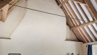 Image of a bedroom eco refurbishment showing traditional exposed timber A frame structure