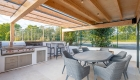 Image of outdoor dining and kitchen/barbecue area with exposed timber structure canopy