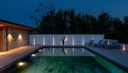 Night time image of the reflective swimming pool and outdoor contemporary art sculpture with directional lighting