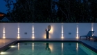 Night time image of the reflective swimming pool and outdoor art sculpture with directional lighting