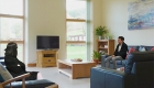 Image of a bright and naturally lit communal living area with tall ceiling and exposed timber ridge beam