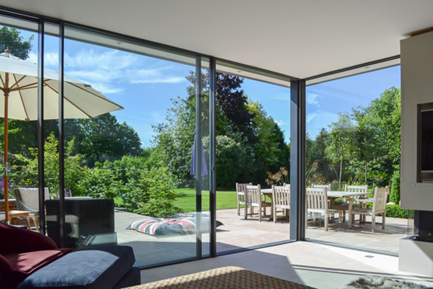 full height windows looking out of a garden room to a beautiful garden beyond