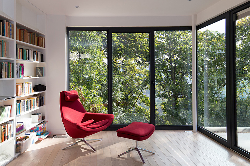 full height windows framing a view of trees from a private library reading room